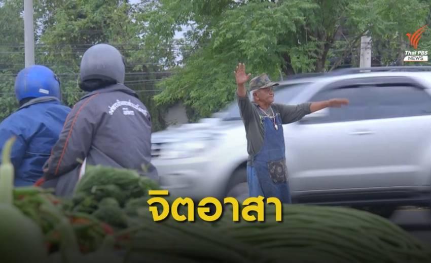พ่อค้าผักจิตอาสายืนโบกรถ เพื่อความปลอดภัยในชั่วโมงเร่งด่วน